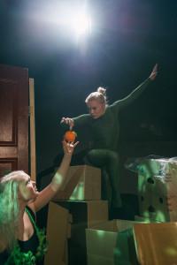 Käärme (Erika Malkki) tarjoaa hedelmää Eevalle (Anna Nekrasova) esityksessä Amatsonia!. Ohjaus Tiina Paananen. Kuva: Jussi Virkkumaa